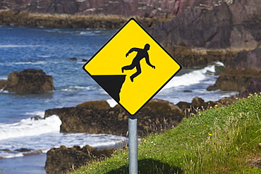 A yellow warning sign depicting a person falling off a cliff, County kerry, ireland