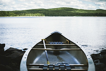 Fiberglass canoe at lakeside with mountain on the horizon, Thetford mines quebec canada