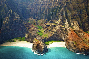 Blue water and white sand in a small inlet along a rugged coastline, Hawaii united states of america