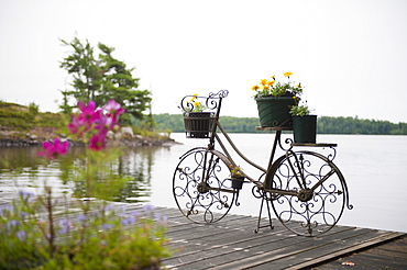 A deck on a lake with a decorative flower pot in the shape of a bicycle, kenora ontario canada