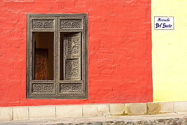 A Window With Ornate Gold Trim And Shutters On A Building Painted Red And Yellow, Lima, Peru