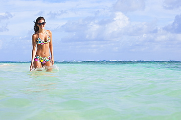 A Woman Standing In The Ocean Wearing A Colourful Bikini And Sunglasses, Punta Cana, La Altagracia, Dominican Republic