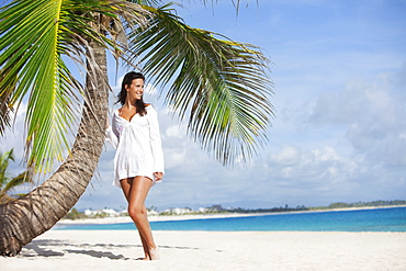 A Woman In A White Dress Posing Beside A Palm Tree On A Beach, Punta Cana, La Altagracia, Dominican Republic