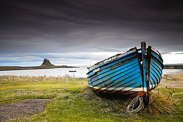 A Weathered Boat Sitting On The Shore With Lindisfarne Castle In The Distance, Lindisfarne, Northumberland, England