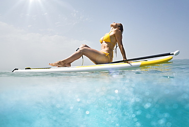 A woman in a yellow bikini sits with her paddle and board basking in the sunlight on the ocean, Tarifa cadiz andalusia spain