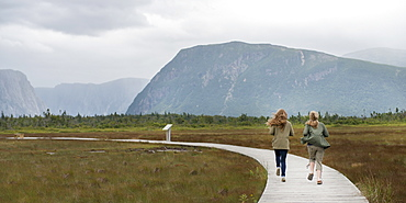 Two Young Women Walking On A Wooden Boardwalk At Norris Point, Newfoundland And Labrador, Canada