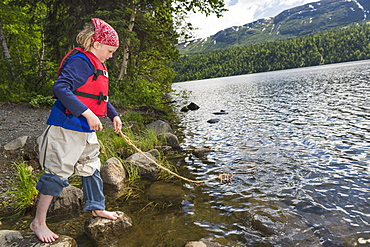 Young Girl With Bare Feet Wearing A Red Bandana And Lifejacket Playing With A Homemade Toy Wood Raft On A String At Byers Lake, Denali State Park, Alaska, United States Of America