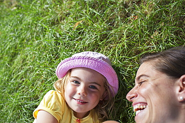 Young Girl Laying On The Grass With Her Mother Laughing, Toronto, Ontario, Canada