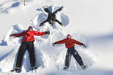 A Family Making Snow Angels In Wintertime, Talkeetna, Alaska, United States Of America