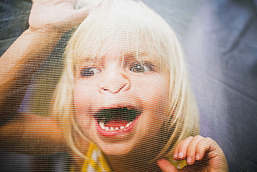 A Young Girl With A Silly Expression On Her Face Viewed Through A Window Screen, Peachland, British Columbia, Canada