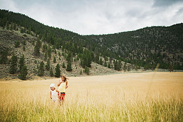 Two Young Girls Walking In The Tall Grass Of A Field, Peachland, British Columbia, Canada