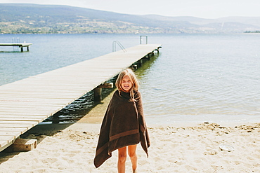A Girl Stands On The Beach At The Edge Of Lake Okanagan, Peachland, British Columbia, Canada