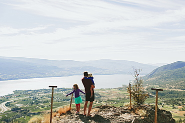 A Father With His Daughters Standing On A Rock Ledge Overlooking Lake Okanagan, Peachland, British Columbia, Canada