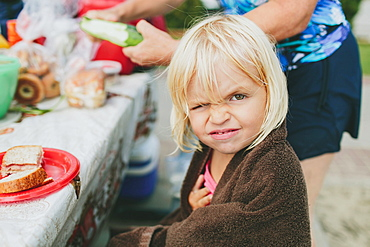 A Young Girl Winking At The Camera As She Sits At A Picnic Table For A Meal, Peachland, British Columbia, Canada