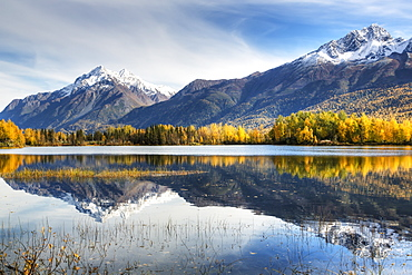 The Snowcapped Chugach Mountains And Autumn Foliage Reflecting In Reflections Lake Along The Glenn Highway In The Matanuska Susitna Valley, Alaska, United States Of America