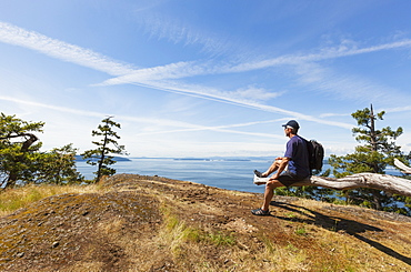A Man Sits Overlooking A Bluff On Pender Island, A Gulf Island Near Vancouver Island, British Columbia, Canada