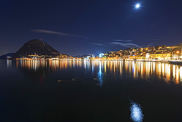 City Lights Illuminated On The Tranquil Lake Lugano, Lugano, Ticino, Switzerland