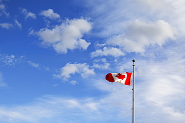 A Canada Flag Flying In The Wind Against A Blue And Cloudy Sky, Fort Mcmurray, Alberta, Canada