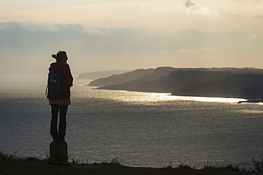 Silhouette Of A Woman Admiring The View Towards Lyme Regis From The Top Of Golden Cap On The Jurassic Coast, Seatown, Dorset, England