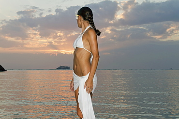 A Woman In A White Bikini And A Tropical Flower In Her Hair Poses In The Water At Sunset, Honolulu, Hawaii, United States Of America