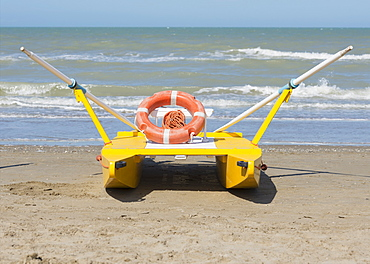 A Lifeboat Sitting On The Beach At The Water's Edge, Rimini, Emilia-Romagna, Italy