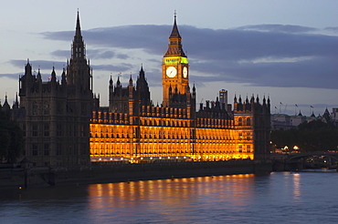 A Building And Clock Tower Along The Water's Edge Illuminated At Dusk, London, England