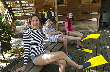 A Mother And Two Daughters Sit On A Wooden Bench With Flippers On Their Feet, Utila Island, Honduras