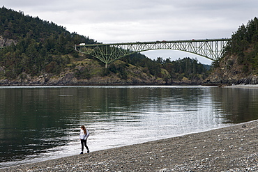A Young Woman Walks On A Rocky Beach In Deception Pass State Park, Oak Harbor, Washington, United States Of America