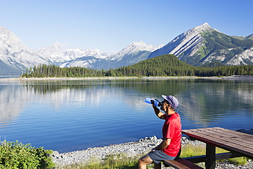 A Man Drinks From A Water Bottle On The Edge Of A Lake Overlooking The Rocky Mountains, Kananaskis, Alberta, Canada