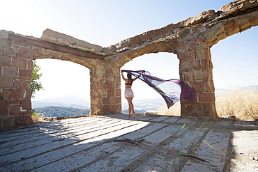 A Woman Holding A Piece Of Sheer Fabric Behind Her As It Flows In The Wind Within Some Ruined Arches, Santa Barbara, California, United States Of America