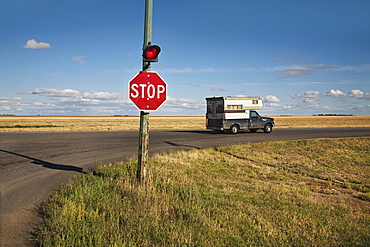 A Stop Sign And Red Light At An Intersection, Saskatchewan, Canada
