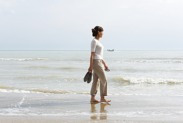 A Woman Walking On The Wet Beach Carrying Her Shoes, Rimini, Emilia-Romagna, Italy