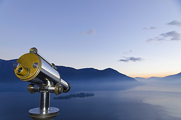 Binoculars With A View Of A Mountainous Landscape And Fog Over Lake Maggiore, Isole Di Brissago, Ticino, Switzerland