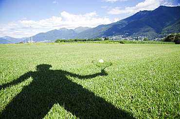 Shadow of a person holding a racquet being cast onto a ball sitting on the grass, Locarno ticino switzerland