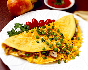 Food - Cheese and Mushroom Omelette garnished with chopped green onions (scallions) and pear tomatoes.
