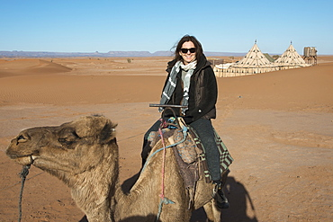 A woman riding a camel on the erg chegaga dunes, Souss-massa-draa morocco
