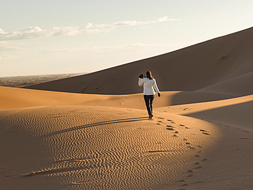 A woman walking on a sand dune, Sous-massa-draa morocco
