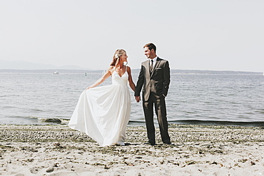 A bride and groom on a beach at the water's edge, Kirkland washington united states of america