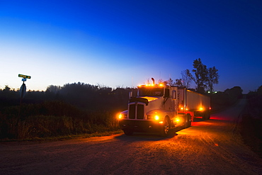 Agriculture - A grain truck at a country road intersection at dusk in route to a grain elevator with a load of freshly harvested corn / near Northland, Minnesota, USA.