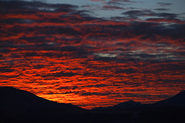 Dramatic Red Sunset Over Silhouetted Landscape, New Zealand