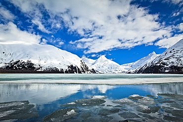 Snow Covered Mountain Peaks Reflected On The Half Frozen Portage Lake, Chugach National Forest, Alaska, United States Of America