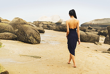 A Model In Formal Dress Walks Barefoot On The Sandy Beach, Xiamen, China