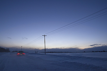 Car Travelling Along Old School Road At Dusk In Winter, Caledon, Ontario, Canada