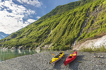 Two Kayaks On The Beach In Front Of Green Mountain With Waterfall At Shoup Bay State Marine Park, Prince William Sound, Valdez, Alaska, United States Of America