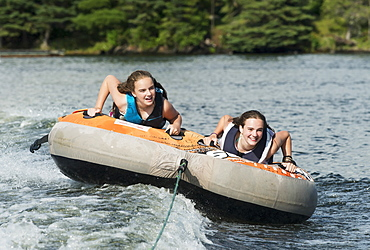 Two Teenage Girls Riding In An Inner Tube Being Pulled By A Boat On A Lake, Ontario, Canada