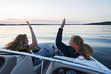 Two Teenage Girls Riding In The Front Of A Boat On A Tranquil Lake At Sunset Giving Each Other A High Five, Ontario, Canada