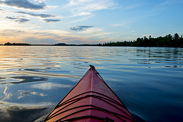 Bow Of A Canoe On A Tranquil Lake At Sunset, Ontario, Canada