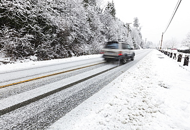 A Vehicle Makes Its Way On Snow Covered Roads On Vancouver Island, Duncan, British Columbia, Canada