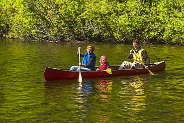 A Couple And Young Girl In A Red Canoe On Byers Lake With Green Forested Shoreline In Byers Lake Campground, Denali State Park, Alaska, United States Of America