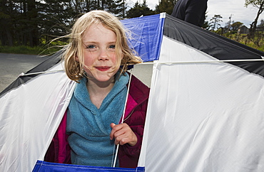 Young Girl Holding A Kite With Her Head Poking Through An Opening In The Kite, Bishops Beach, Katchemak Bay, Homer, Alaska, United States Of America